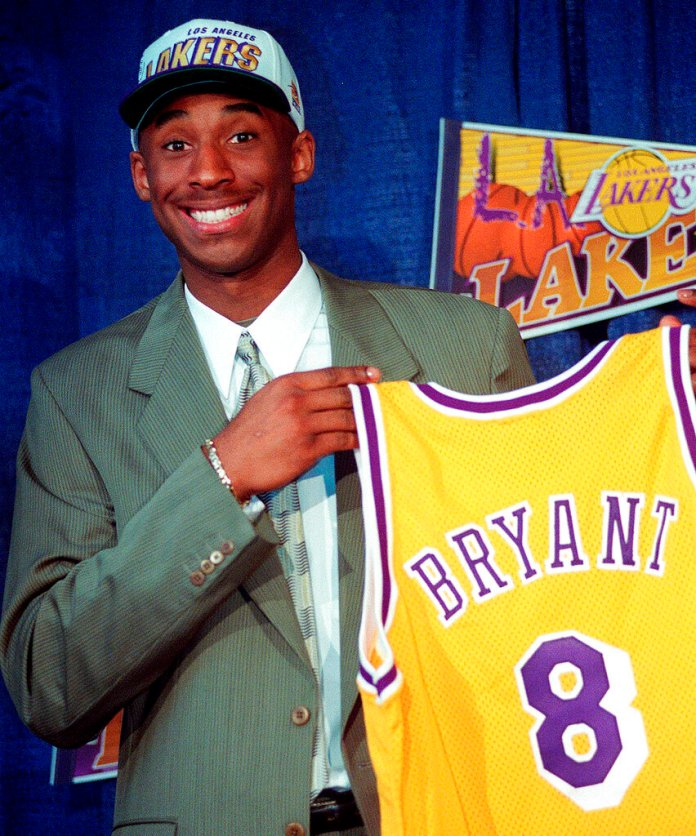 Kobe Bryant, then 17, jokes with the media as he holds his Los Angeles Lakers jersey during a news conference at the Great Western Forum in Inglewood, Calif. Bryant, a five-time NBA champion and a two-time Olympic gold medalist, died in a helicopter crash in California on Sunday. He was 41.  Photo courtesy of Susan Sterner/AP Photo