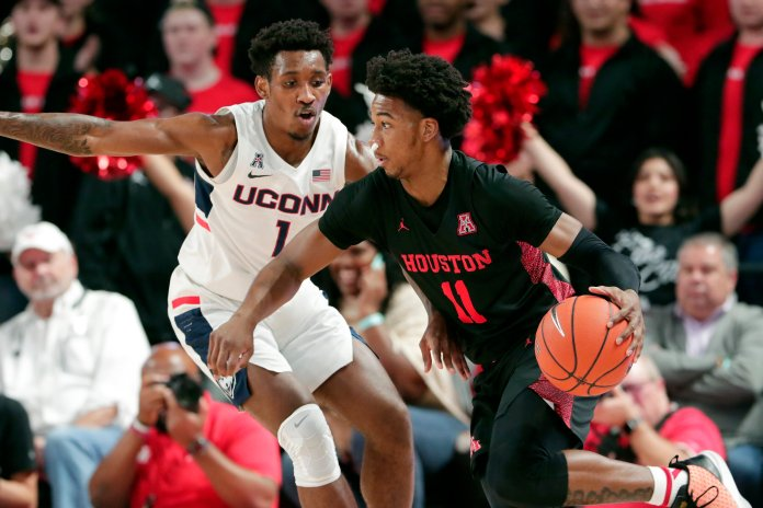 Houston guard Nate Hinton (11) drives around Connecticut guard Christian Vital (1) during the first half of an NCAA college basketball game Thursday, Jan. 23, 2020, in Houston. (AP Photo/Michael Wyke)