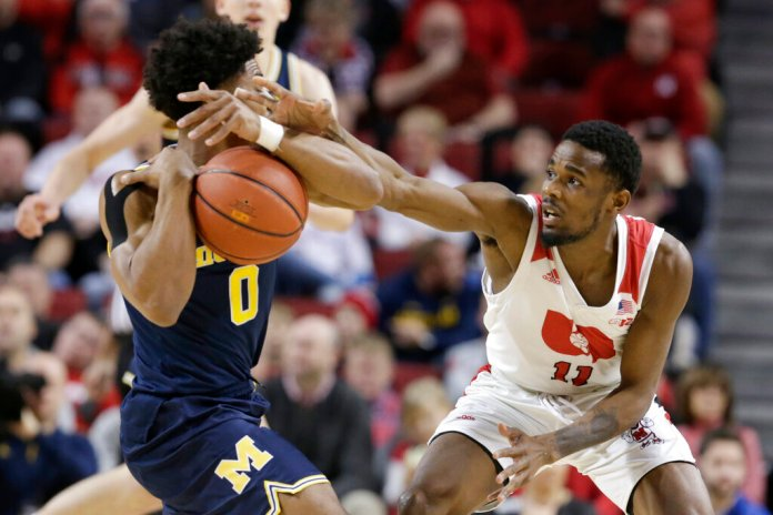 Nebraska's Dachon Burke Jr. (11) reaches for the ball held by Michigan's David DeJulius (0) during the first half of an NCAA college basketball game in Lincoln, Neb., Tuesday.  Photo courtesy of Nati Harnik/AP Photo