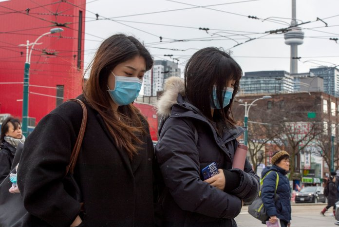 Pedestrians wear protective masks as they walk in Toronto on Monday, Jan. 27, 2020. Canada's first presumptive case of the novel coronavirus has been officially confirmed, Ontario health officials said Monday as they announced the patient's wife has also contracted the illness. (Frank Gunn/The Canadian Press via AP)
