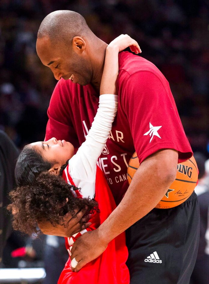 Los Angeles Lakers Kobe Bryant (24) hugs his daughter Gianna on the court in warm-ups before first half NBA All-Star Game basketball action in Toronto. Bryant, his 13-year-old daughter, Gianna, and several others are dead after their helicopter went down in Southern California on Sunday, Jan. 26, 2020. (Mark Blinch/The Canadian Press via AP)