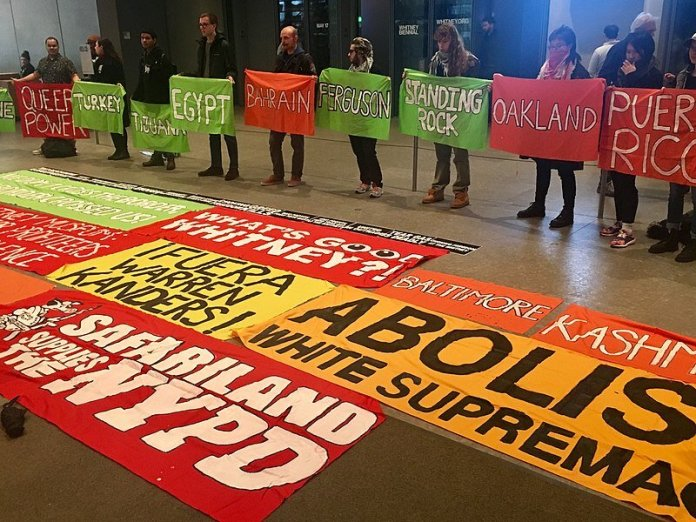 April 5, 2019 protest by Decolonize This Place at the Whitney Museum, New York NY, over board vice chair Warren Kanders' ownership of Safariland, a manufacturer of tear gas and other weapons.   Photo in the public domain via    Wikimedia Commons