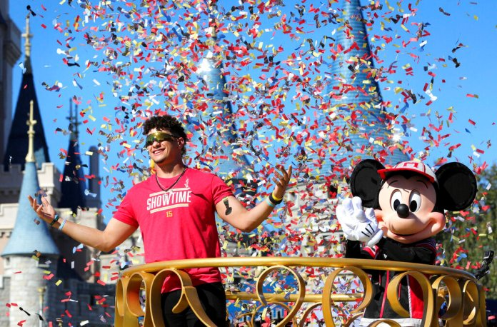 Under a shower of confetti, Kansas City Chiefs quarterback Patrick Mahomes, left, responds to cheering fans with Mickey Mouse during a parade in the team's honor at the Magic Kingdom at Walt Disney World, in Lake Buena Vista, Fla., Monday, Feb. 3, 2020.   Photo by Joe Burbank/AP