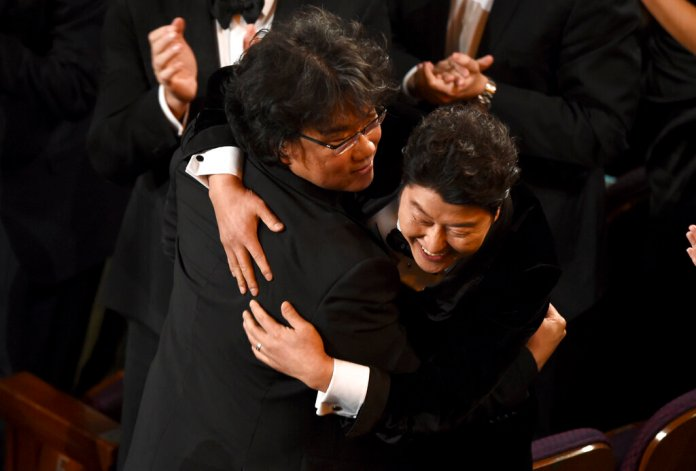 """Bong Joon Ho, left, and Song Kang-Ho celebrate before going on stage to accept the award for best picture for """"Parasite""""at the Oscars on Sunday, Feb. 9, 2020, at the Dolby Theatre in Los Angeles.   Photo by Chris Pizzello/AP"""