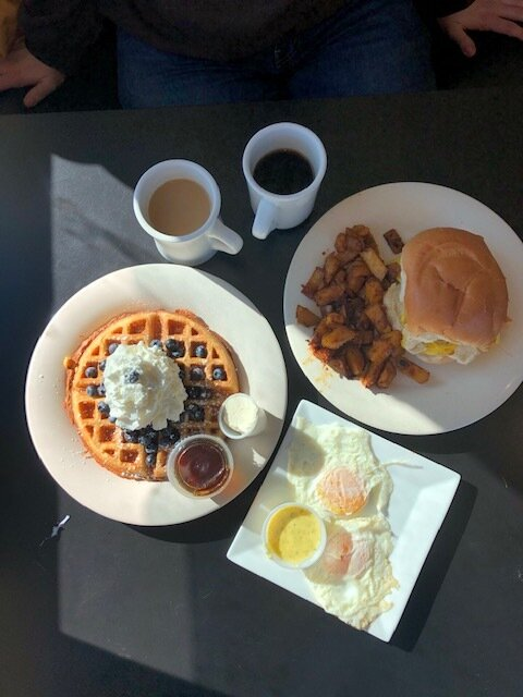 A photo of waffles, home fries, a western breakfast sandwich, and two eggs with hollandaise sauce. The latest brunch spot visited is the River and Rail Cafe.  Photo by Olivia Hickey/The Daily Campus