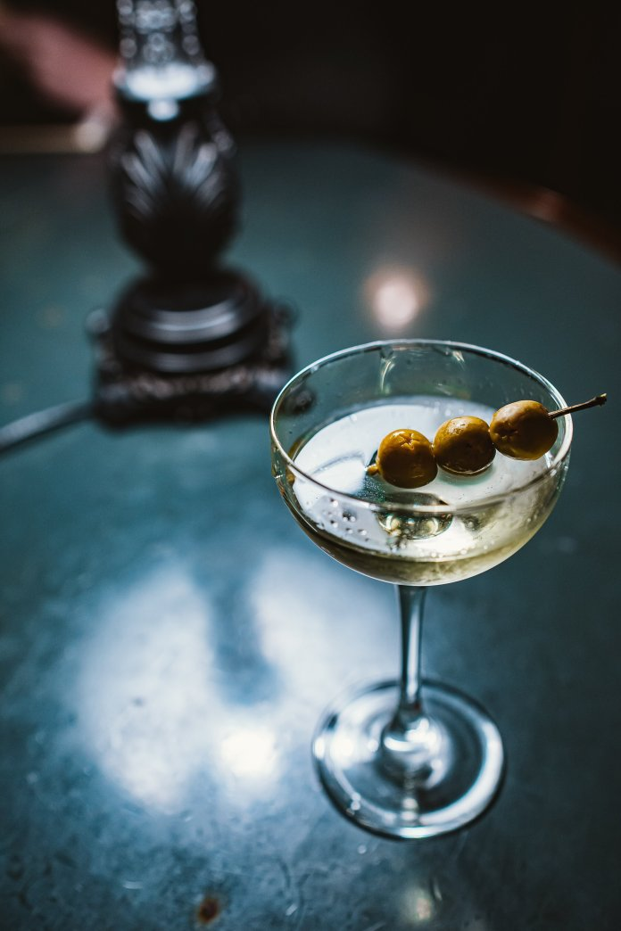 A photo of a martini in a glass. Martinis may have always seemed like a wealthy drink, but now you can easily make one from the comfort of your home.  Photo by   Stanislav Ivanitskiy   on   Unsplash