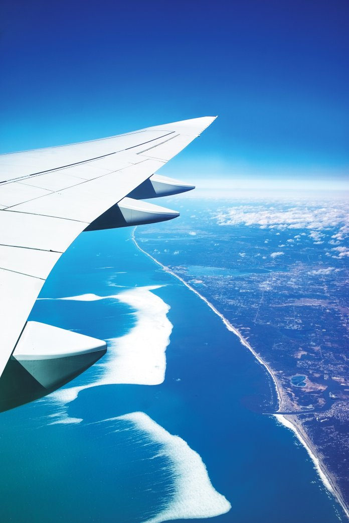 The view from a plane departing from a vacation destination. Flying is a common way to reach your travel destination during spring break.  Photo by    Simon Maage    on    Unsplash