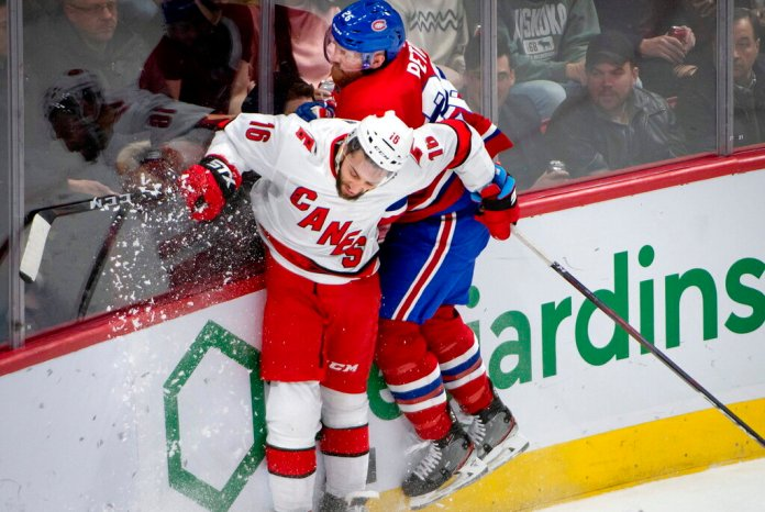 Carolina Hurricanes' Vincent Trocheck, left, and Montreal Canadiens defenseman Jeff Petry (26) crash into the boards while vying for the puck during the second period of an NHL hockey game Saturday, Feb. 29, 2020, in Montreal.  Photo by Peter McCabe/AP