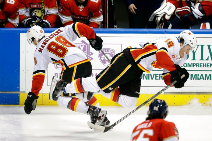 Calgary Flames left wings Matthew Tkachuk (19) and Andrew Mangiapane (88) collide during the third period of an NHL hockey game against the Florida Panthers, Sunday, March 1, 2020, in Sunrise, Fla.  Photo by Wilfredo Lee/AP