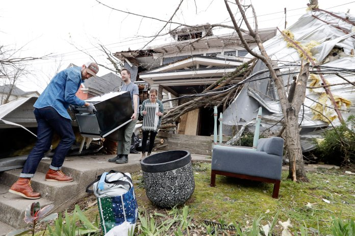 Benji Peck, left, and Austin Grove remove a refrigerator from a damaged home Wednesday, March 4, 2020, in Nashville, Tenn. Residents and businesses face a huge cleanup effort after tornadoes hit the state Tuesday.  Photo courtesy of Mark Humphrey / AP Photo