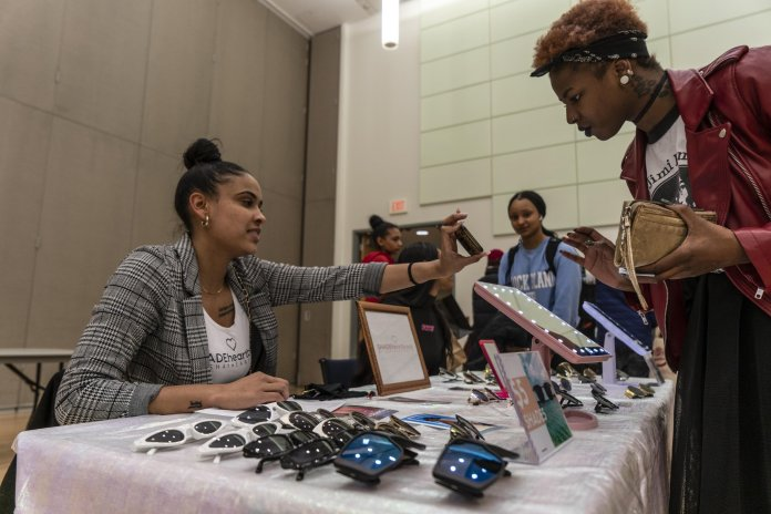 A photo of a transaction happening at the UConn Project Fashion pop-up shop. The pop-up shop featured local designers such as as Toad and SKRS Worldwide. The Daily Campus / Maggie Chafouleas