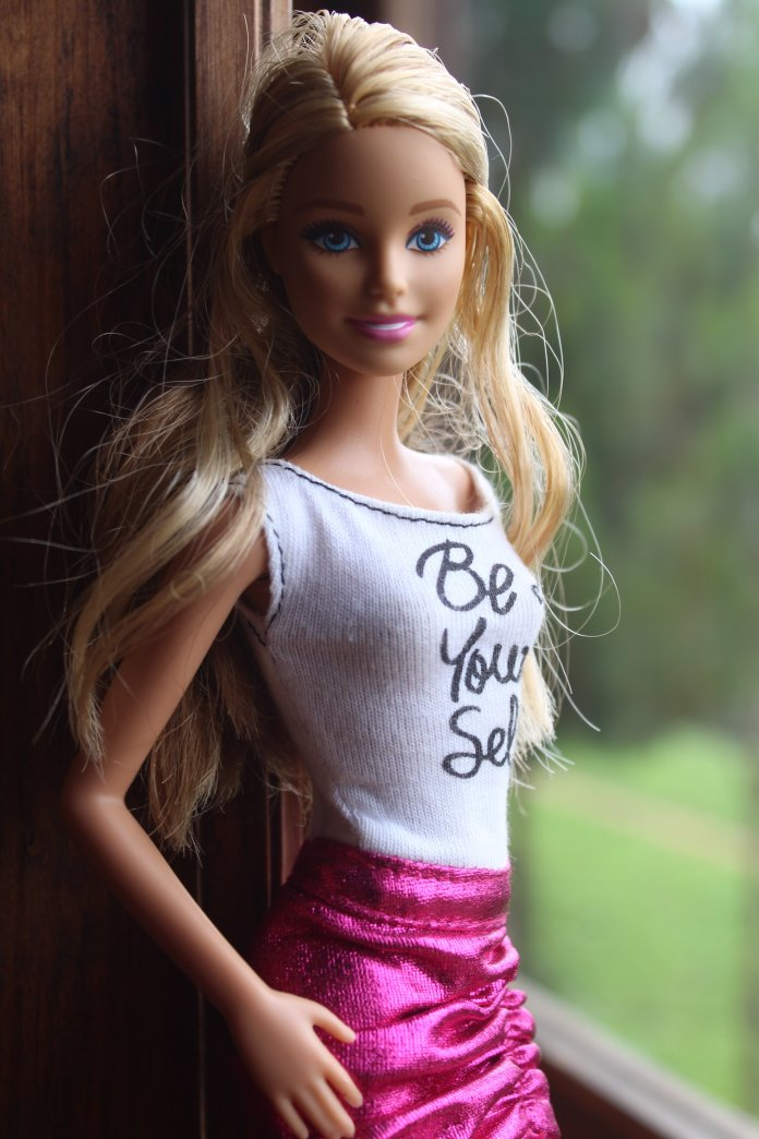 A photo of a Barbie doll next to a window. 61 years ago on March 9th, 1959 the first Barbie doll was released at the American Toy Fair in New York City.  Photo by    Sandra Gabriel    on    Unsplash