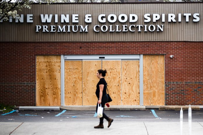 """A pedestrian walks past a boarded up Wine and Spirits store in Philadelphia, Friday, March 20, 2020. Pennsylvania Gov. Tom Wolf directed all """"non-life-sustaining"""" businesses to close their physical locations late Thursday and said state government would begin to enforce the edict starting early Saturday.  Photo by Matt Rourke/AP"""