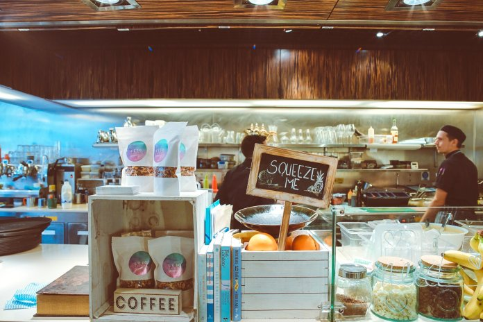 A photo of a small locally owned coffee shop. Local businesses are having to close due to the coronavirus pandemic, and this is causing economic repercussions.  Photo by    Toa Heftiba    on    Unsplash