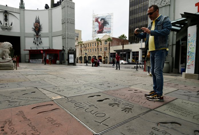 A man takes a picture of the hand and footprints of actor Tom Hanks in the forecourt of the TCL Chinese Theatre, Thursday, March 12, 2020, in the Hollywood section of Los Angeles. Hanks and his wife, actress-singer Rita Wilson, have tested positive for the coronavirus, the actor said in a statement Wednesday. For most people, the new coronavirus causes only mild or moderate symptoms. For some it can cause more severe illness.  (AP Photo/Chris Pizzello)