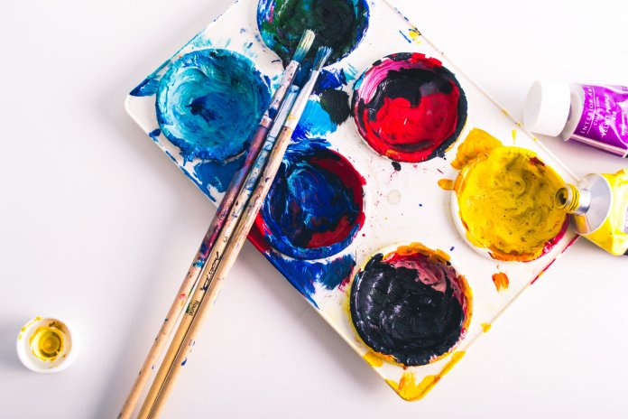 Some paint and paintbrushes on a table. Painting is a great hobby to pick up or resurrect during quarantine.  Photo by    Steve Johnson    on    Unsplash