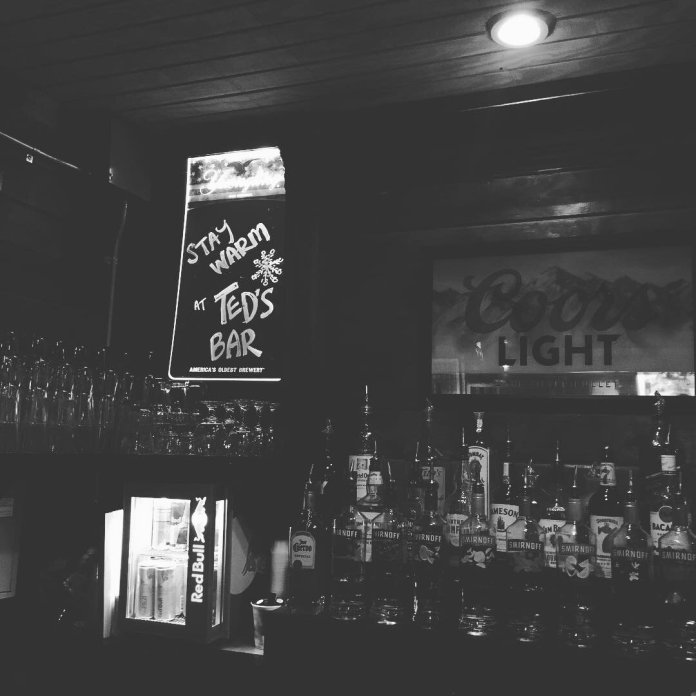 A black and white photo of the beer selection at Ted's Bar. Ted's Bar is a student favorite, and will be missed greatly during quarantine.  @tedsbar