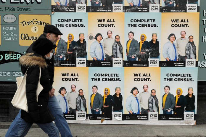 In this Wednesday, April 1, 2020 file photo, People walk past posters encouraging participation in the 2020 Census in Seattle's Capitol Hill neighborhood. (AP Photo/Ted S. Warren, File)