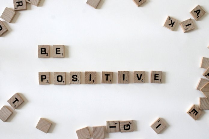 A photo of scrabble tiles laid out spelling the words 'be positive.' Its important to stay positive in light of all of the negativity around us.  Photo by    Amanda Jones    on    Unsplash