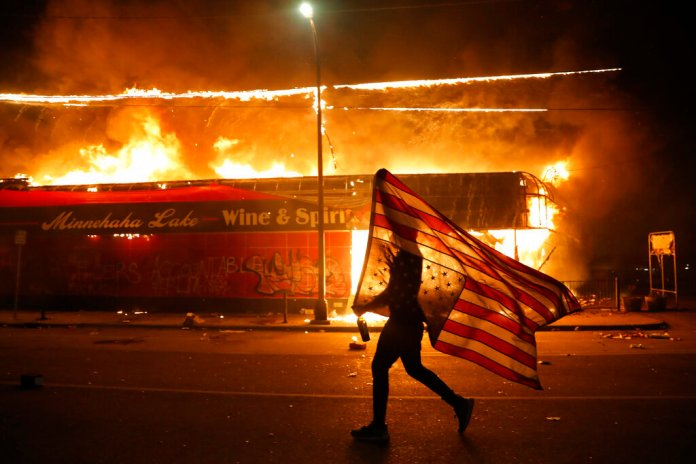 In this Thursday, May 28, 2020 file photo, a protester carries a U.S. flag upside down, a sign of distress, next to a burning building in Minneapolis. Protests over the death of George Floyd, a black man who died in police custody Monday, broke out in Minneapolis for a third straight night.  By Julio Cortez/AP