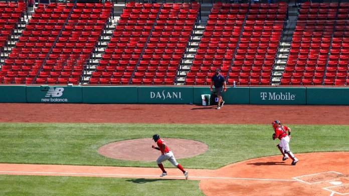 Boston Red Sox's Xander Bogaerts dashes down the first base line in front of empty stands on his ground out during an intra-squad baseball game at Fenway Park on Thursday, July 9, 2020, in Boston. At right is catcher Christian Vazquez.  Photo by Charles Krupa/AP