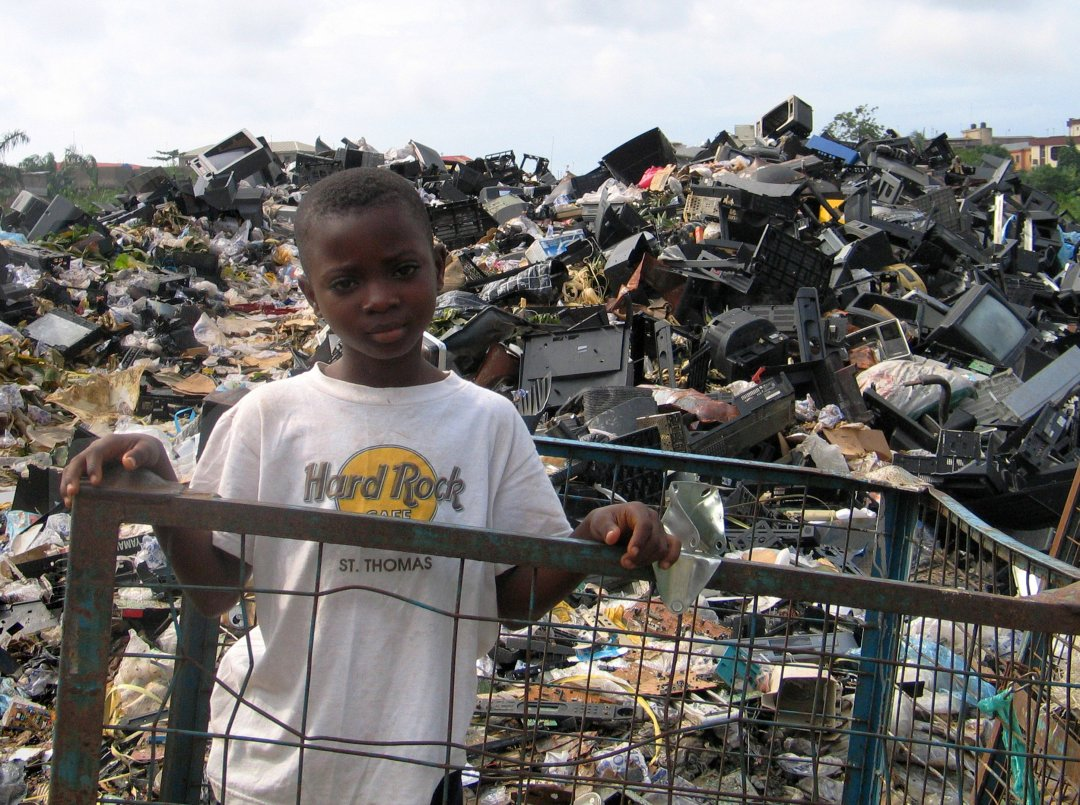 Market scavenger at electronic waste dump of unrepairable, unusable imported e-waste from North America and Europe. Such dumps are set ablaze routinely resulting in highly toxic air emissions. Alaba market, Lagos, Nigeria. Copyright Basel Action Network 2005.