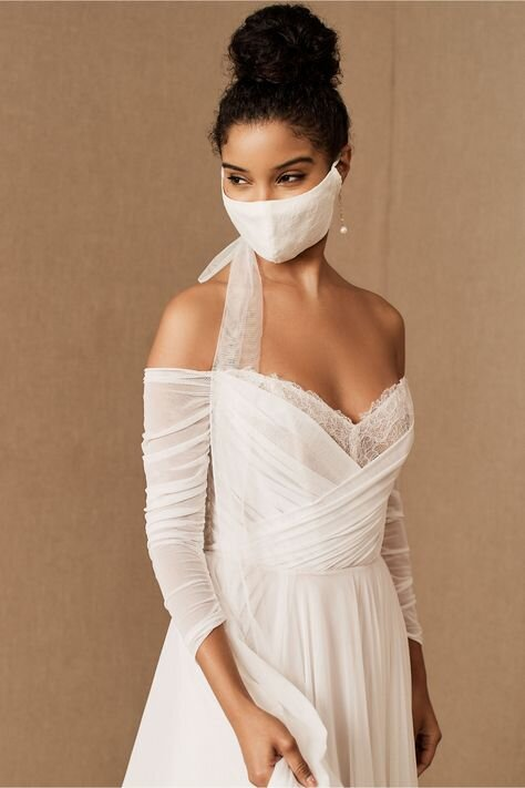 """Anthropologie's BHLDN has dozens of face mask options ranging from dimensional florals with dazzling embellishments like pearls and glass beads to hand-embroidered details to lacy details and soft tulle streamers as seen above in the """"Miles Reusable Face Mask"""" is pretty from face to ears. With white, ivory, neutral, pink, multi, black, blue, green, grey, and silver colors available, matching your mother of the bride to bridesmaid dresses is a snap."""