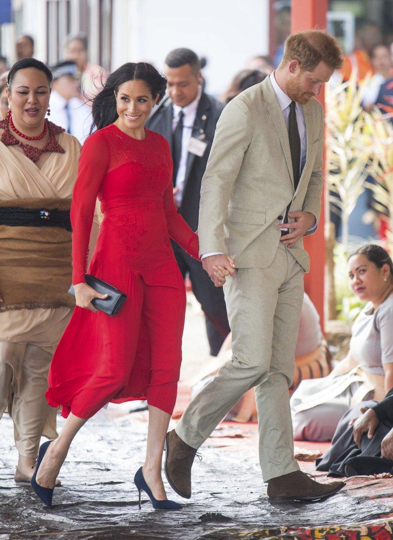 Herzogin Meghan sorgt mit ihrem roten Kleid für einen echten Hingucker.  © picture alliance / AP Photo