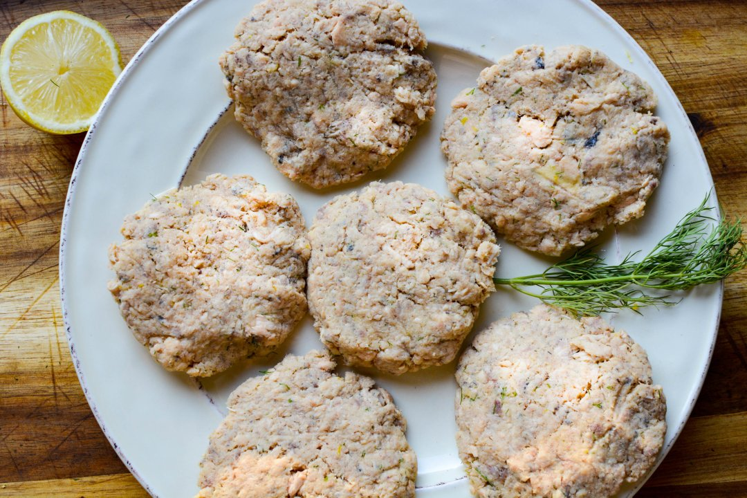 Formed uncooked salmon cakes on plate with Dill and 1/2 lemon