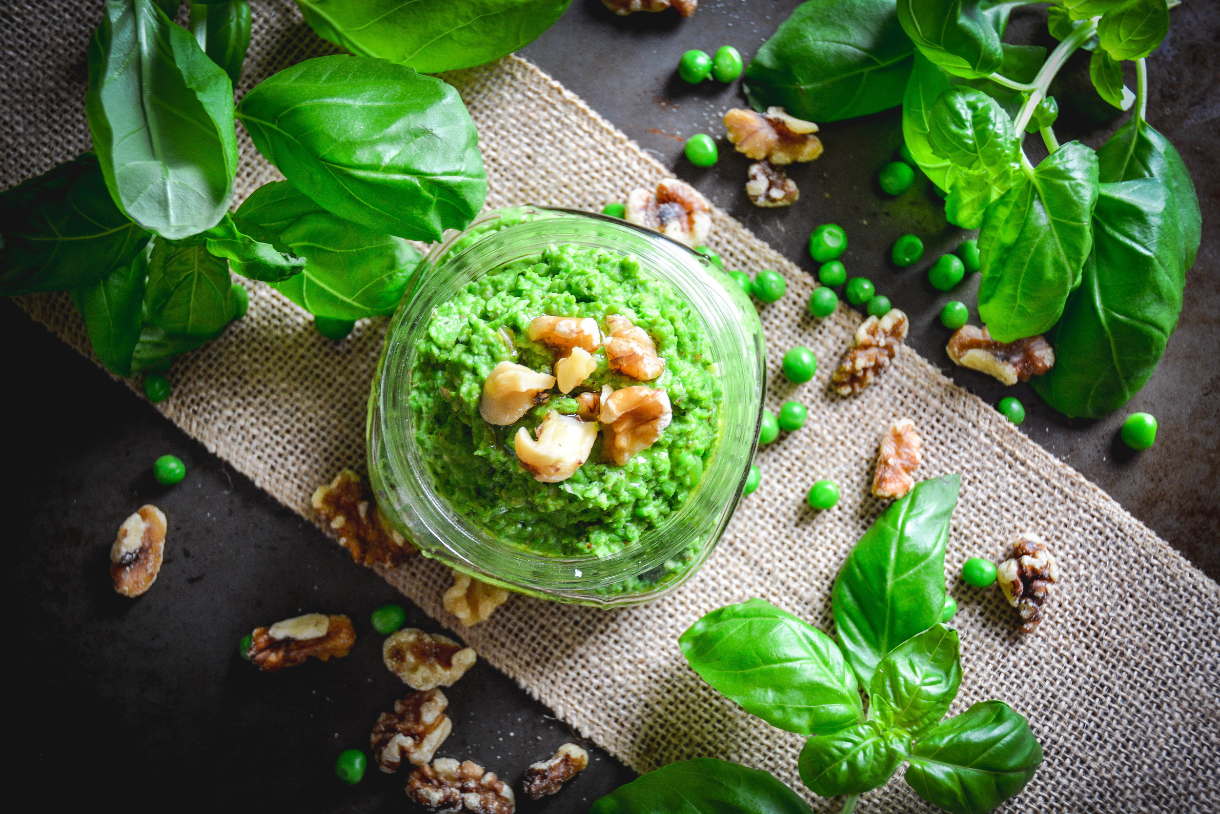 Pea pesto, basil and walnuts on table shot from above
