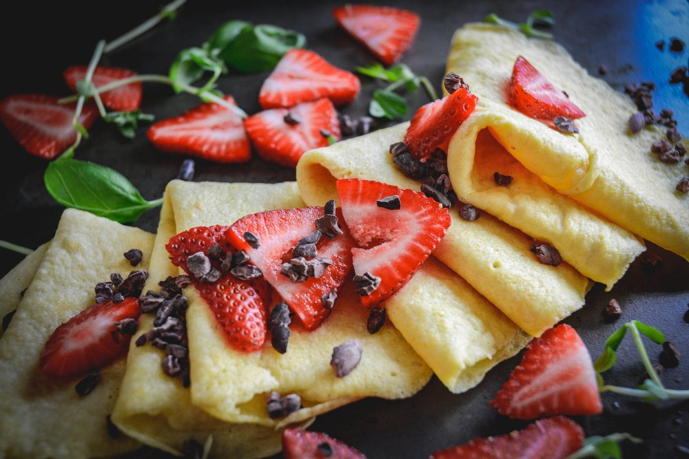 Crepes with slices of strawberries and cacao nibs