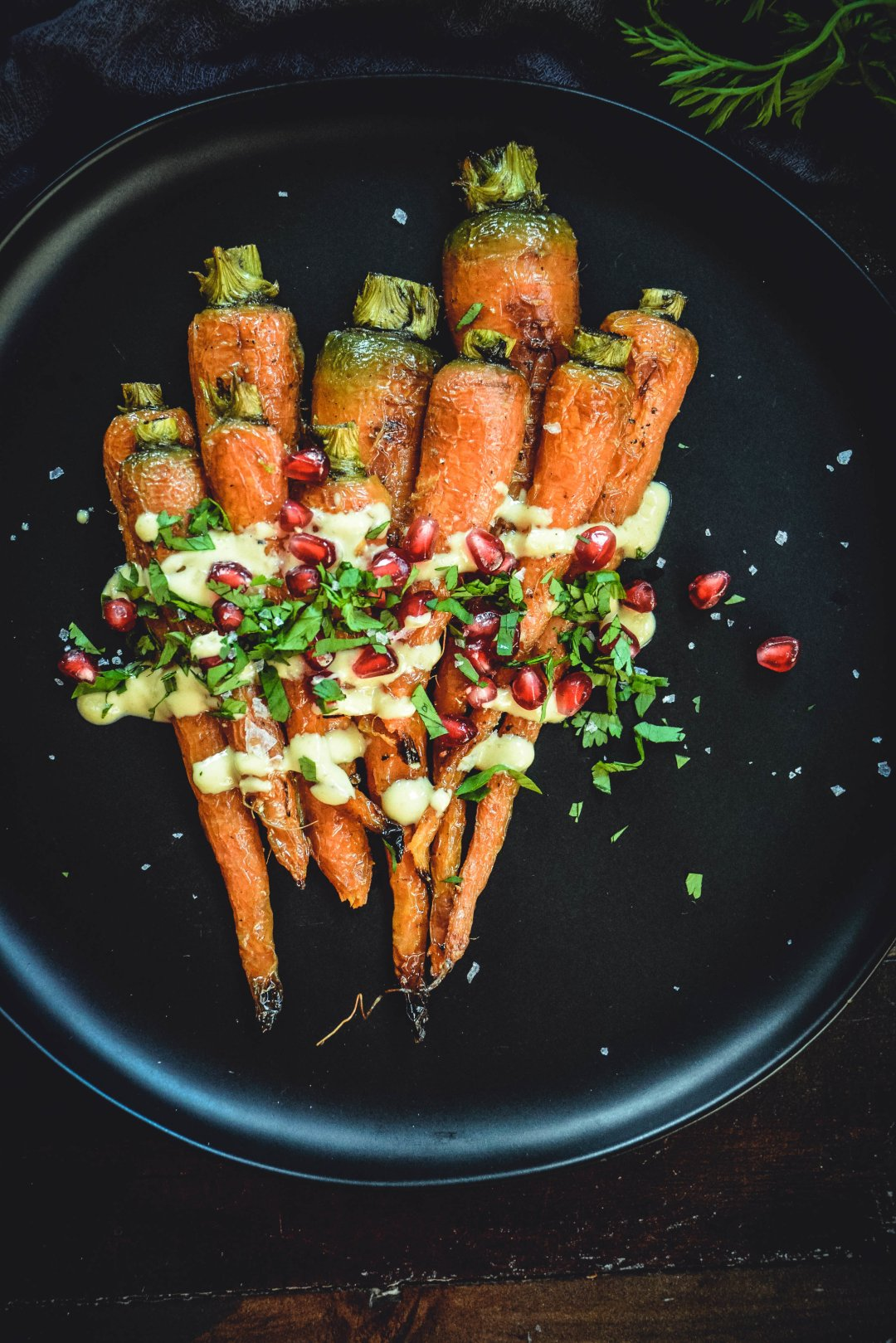 Roasted Carrots With A Simple Orange Tahini Sauce And Pomegranate on black plate