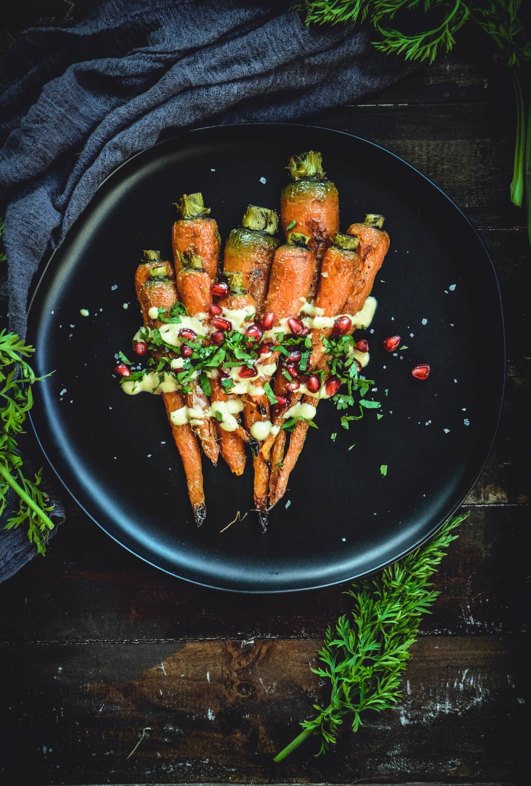 Roasted Carrots With A Simple Orange Tahini Sauce And Pomegranate on black plate with napkin and carrot greens