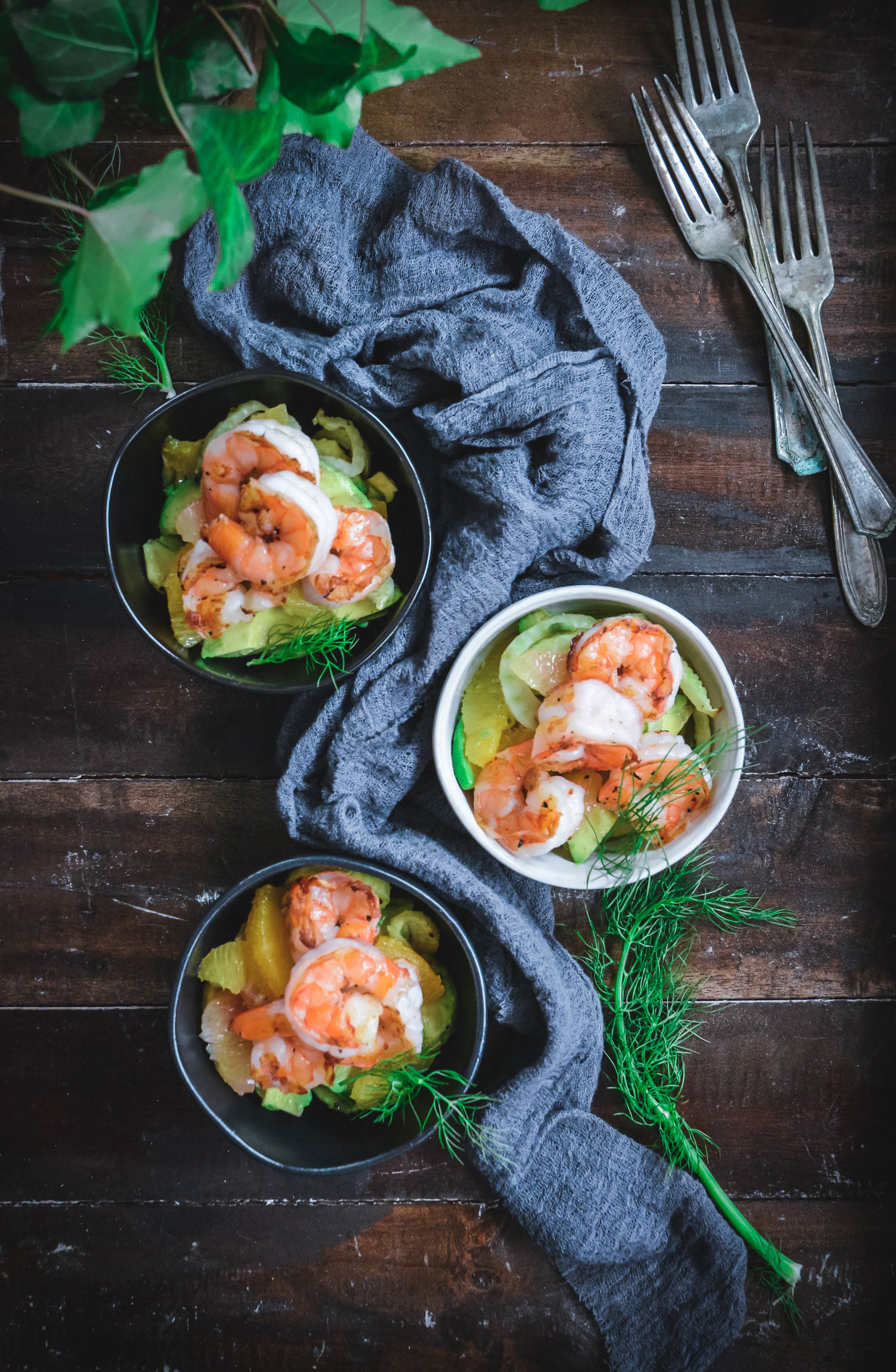 Shrimp Said with Fennel, Citrus and Avocado in 3 bowls with greens, forks and napkin