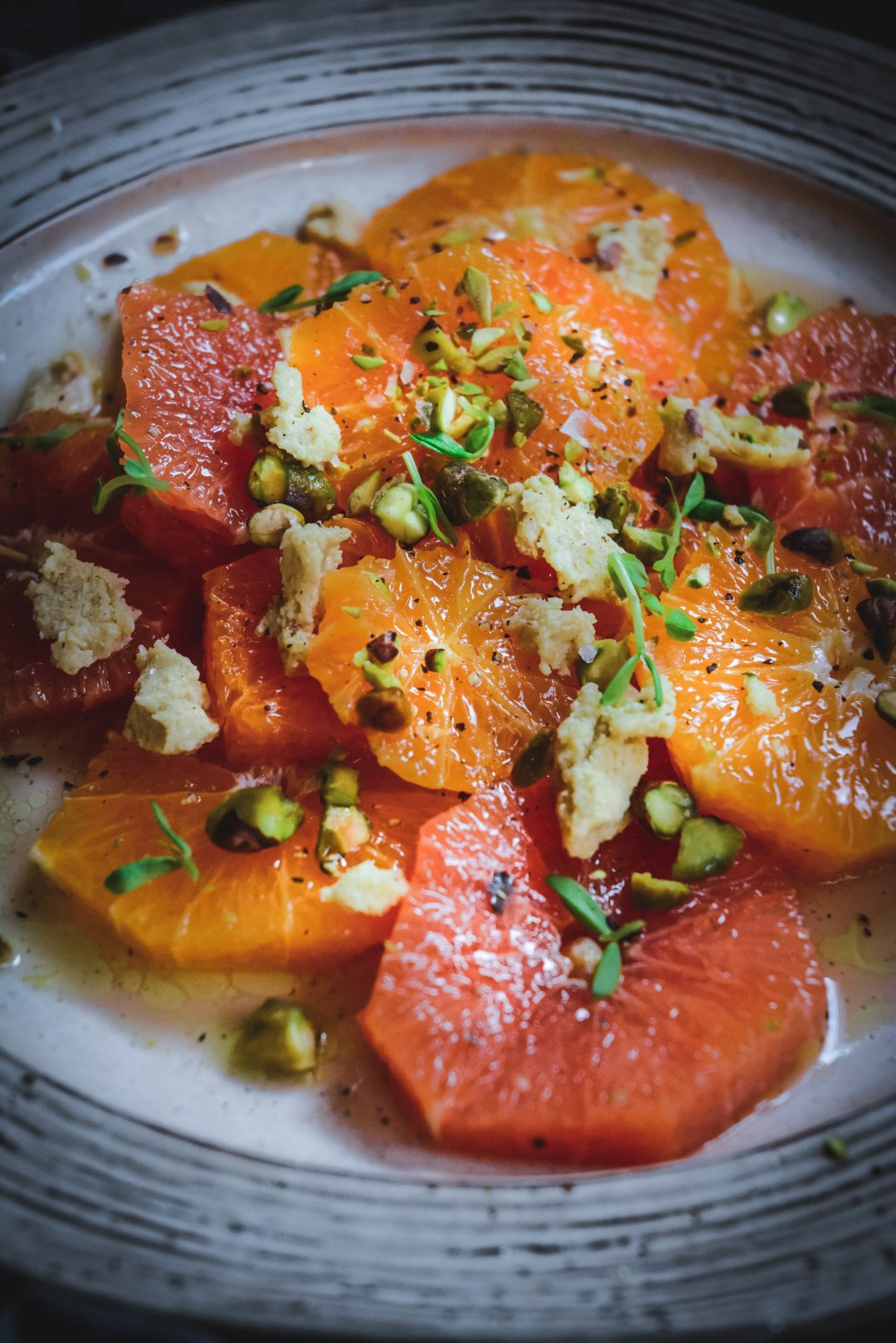 A delicious citrus salad full of flavor. Orange slices are combined with a sweet and salty dressing, topped with cashew cheese, made with nutritional yeast and toasted pistachios. #vegan #citrus #citrussalad #vegansalad #paleosalad #paleofood #paleo #calmeats #orange #cashewcheese #nutritionalyeastrecipes
