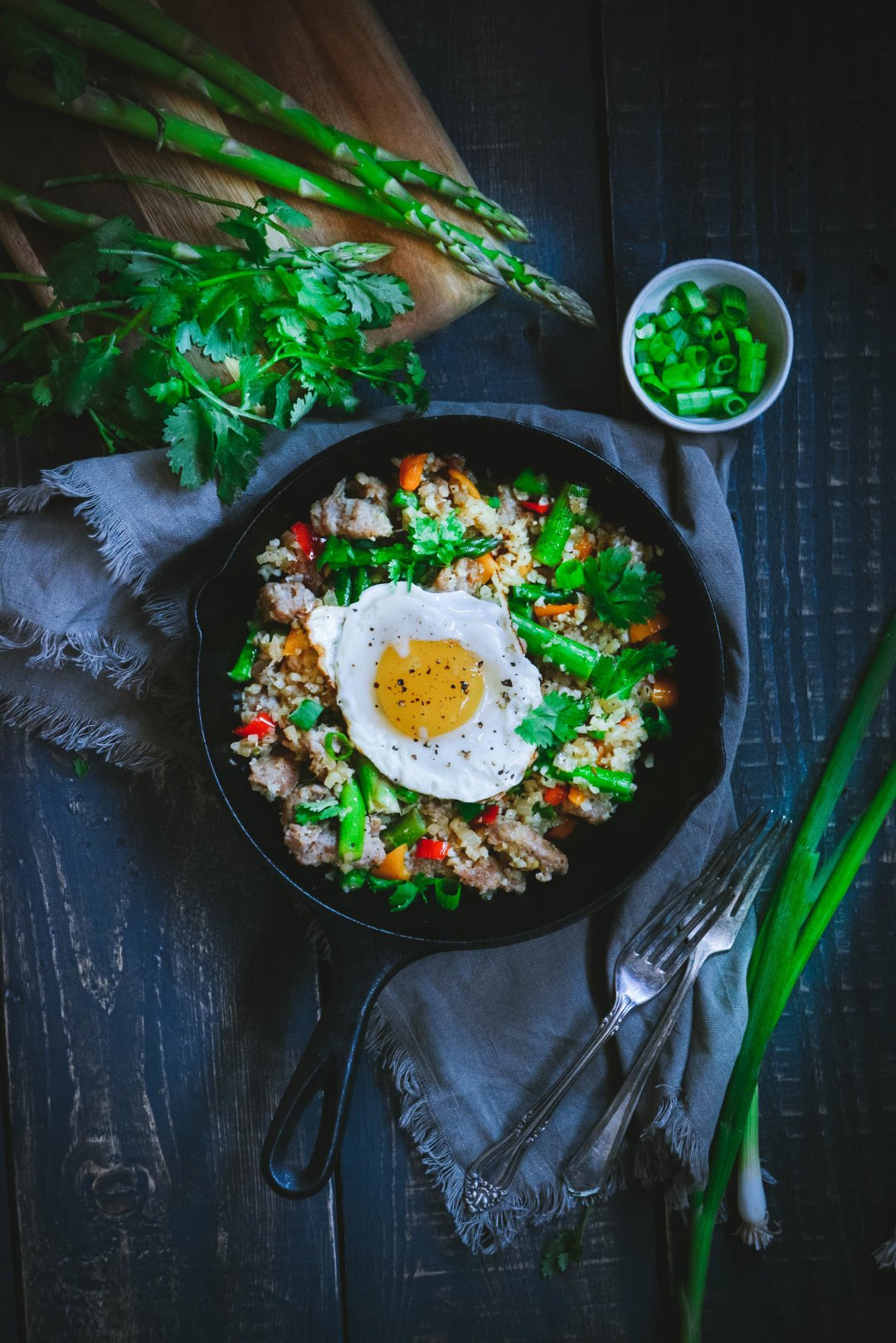 Asparagus sausage scramble with egg, in small pan, with asparagus, cilantro and forks