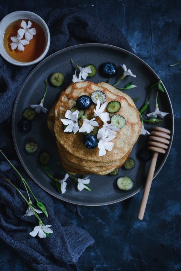 pancakes stacked and topped with flowers and blueberries on plate