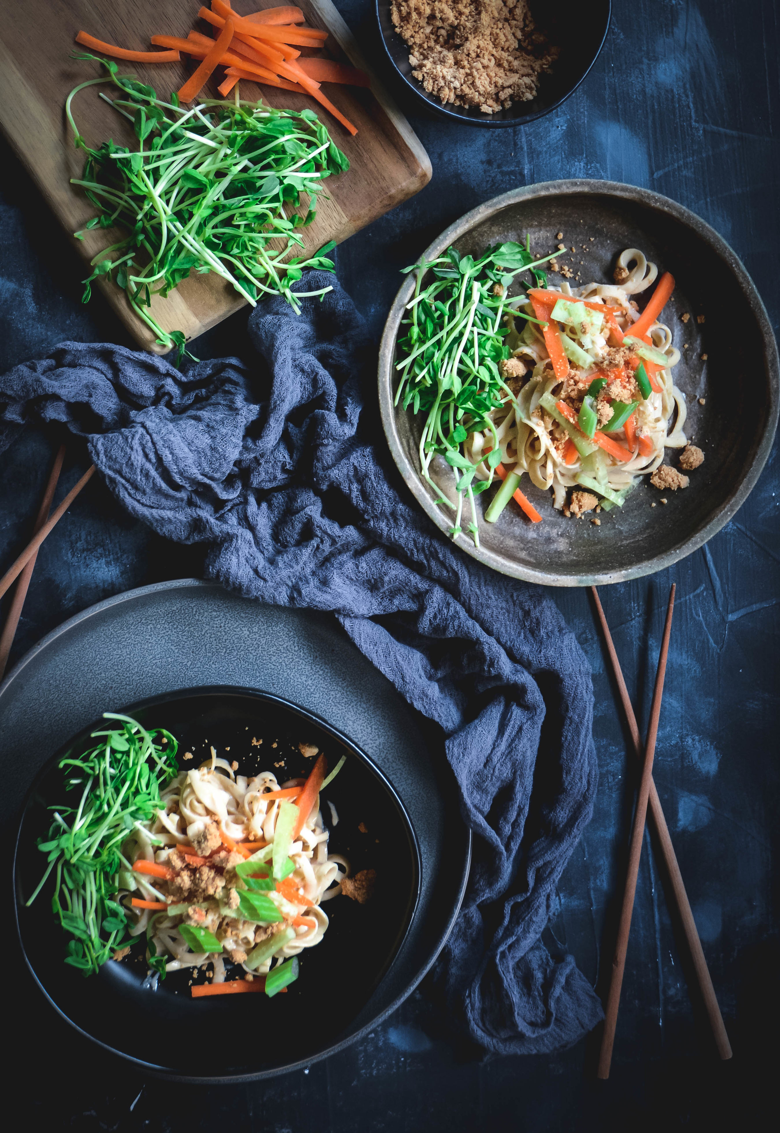 two bowls of noodles with napkin, chopsticks, sprouts carrots and small bowl of rutabaga noodles