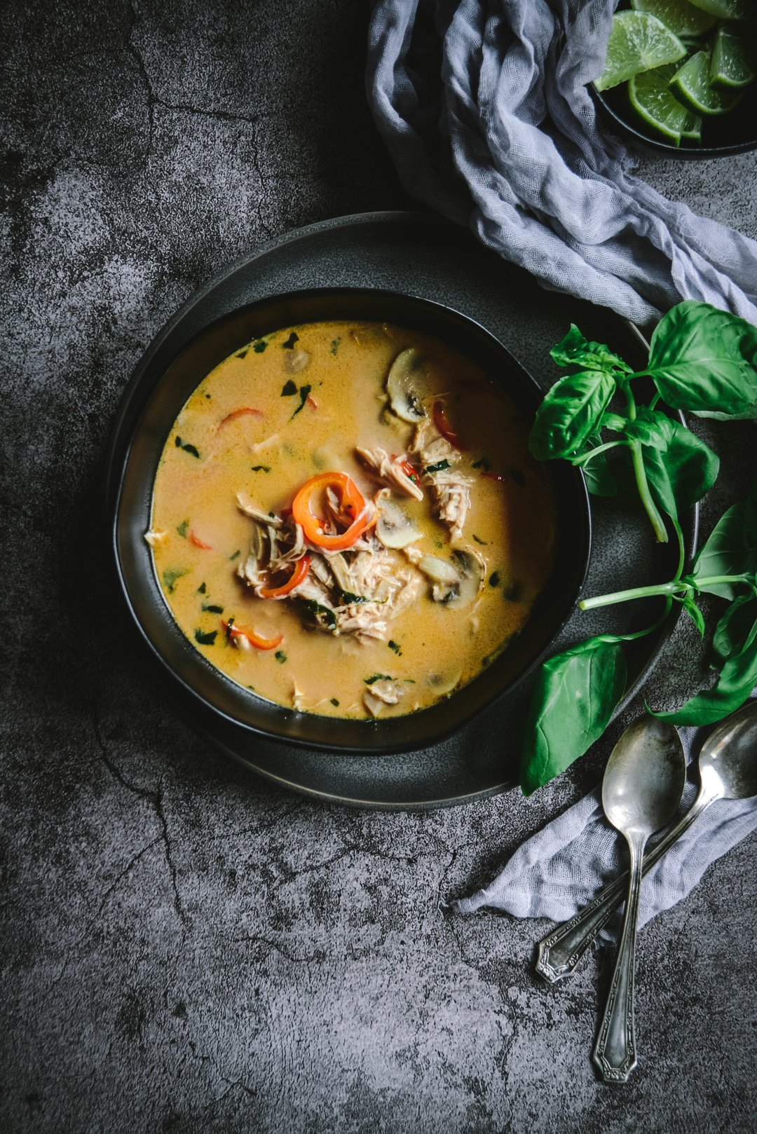 Thai soup in bowl with napkin, basil and spoons