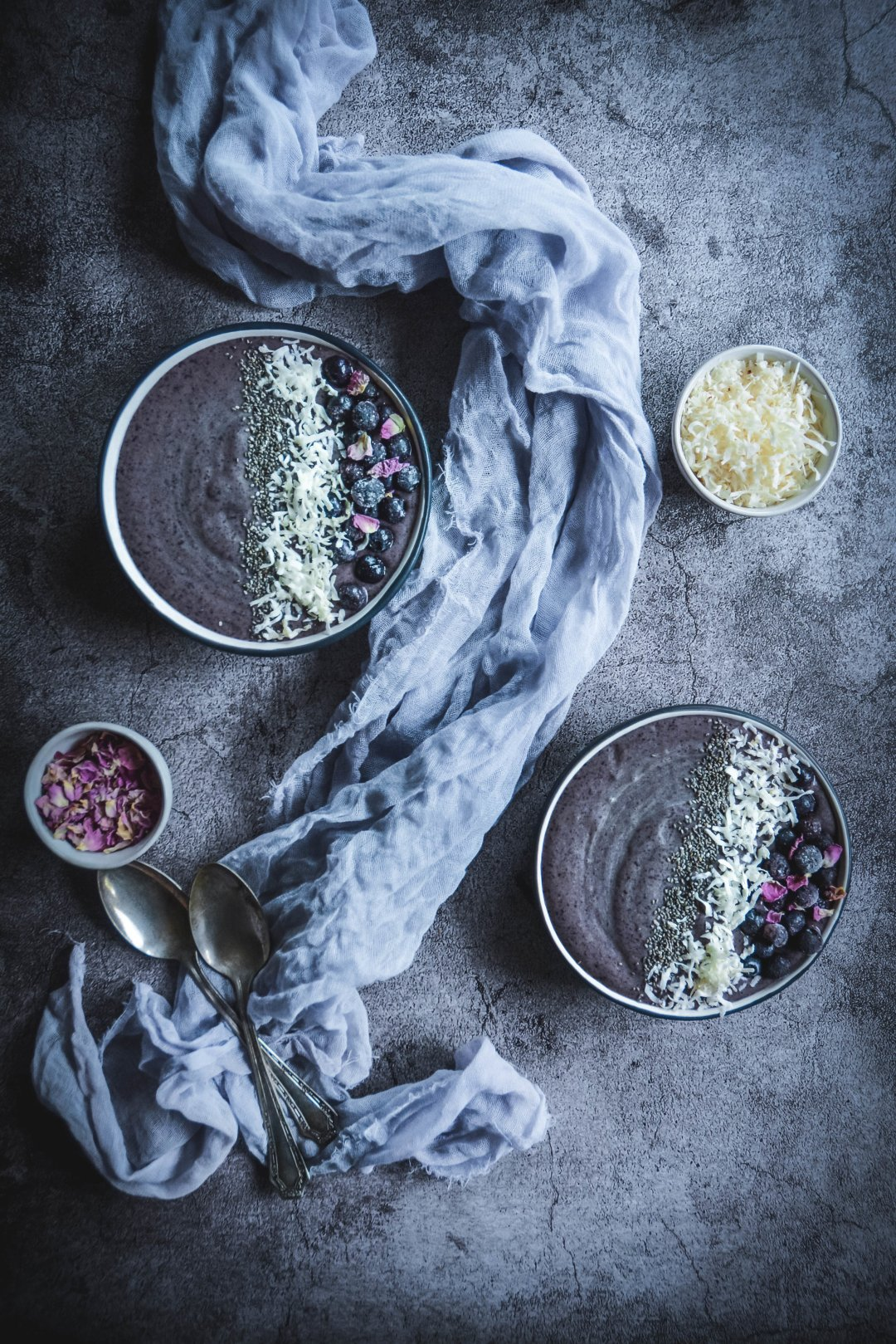 two frozen smoothie bowls, coconut flakes, napkin, spoons, bowl of rose petals