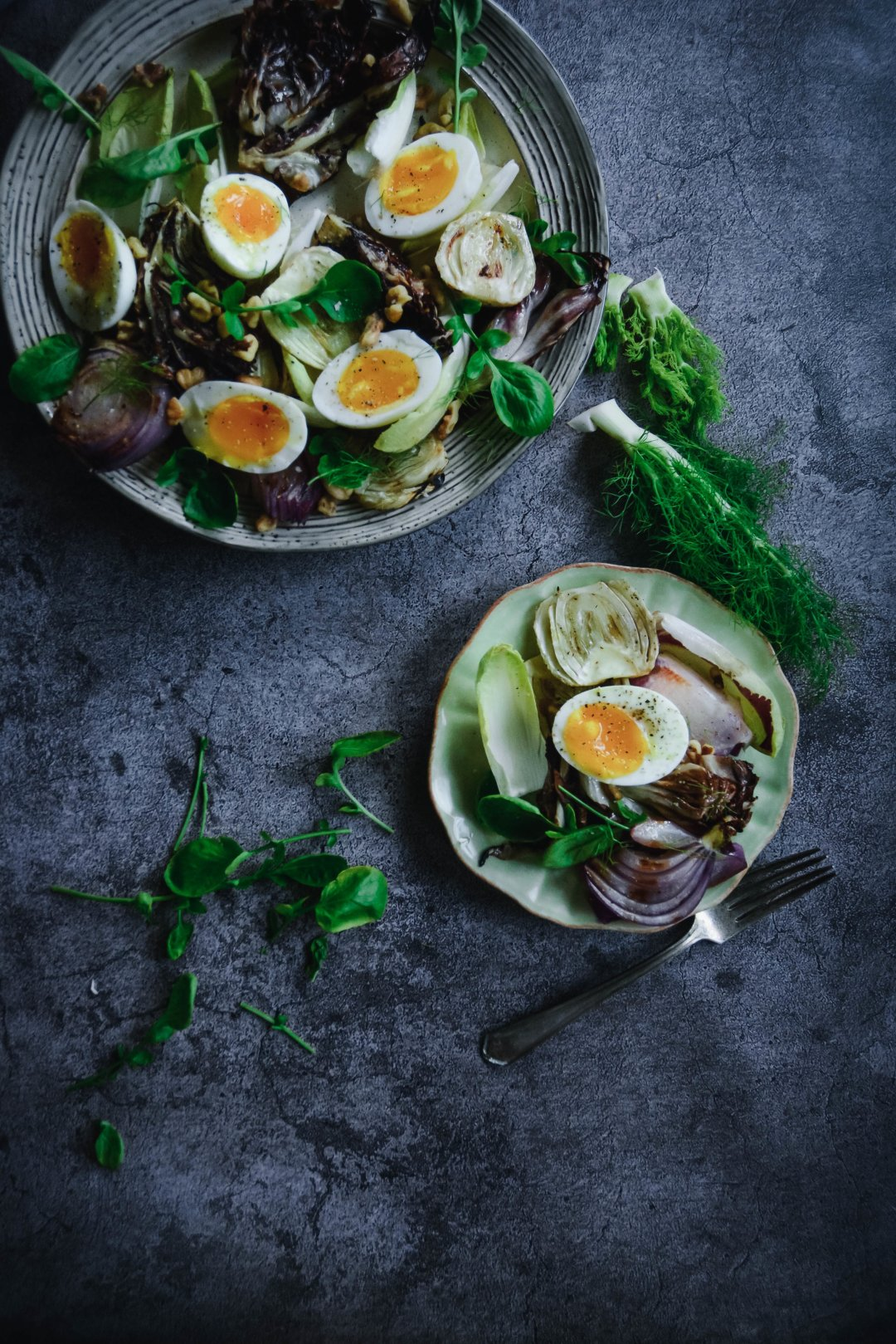 Radicchio salad on two plates topped with eggs