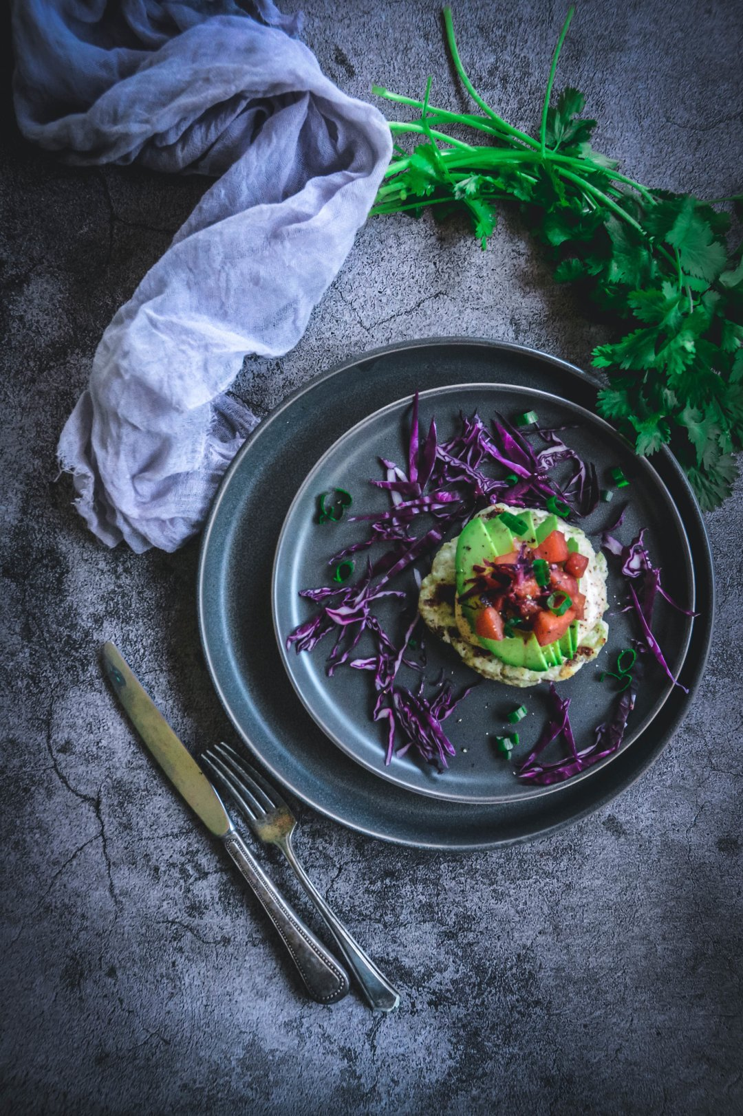 Turkey burgers on plate with fork and knife, cilantro and napkin