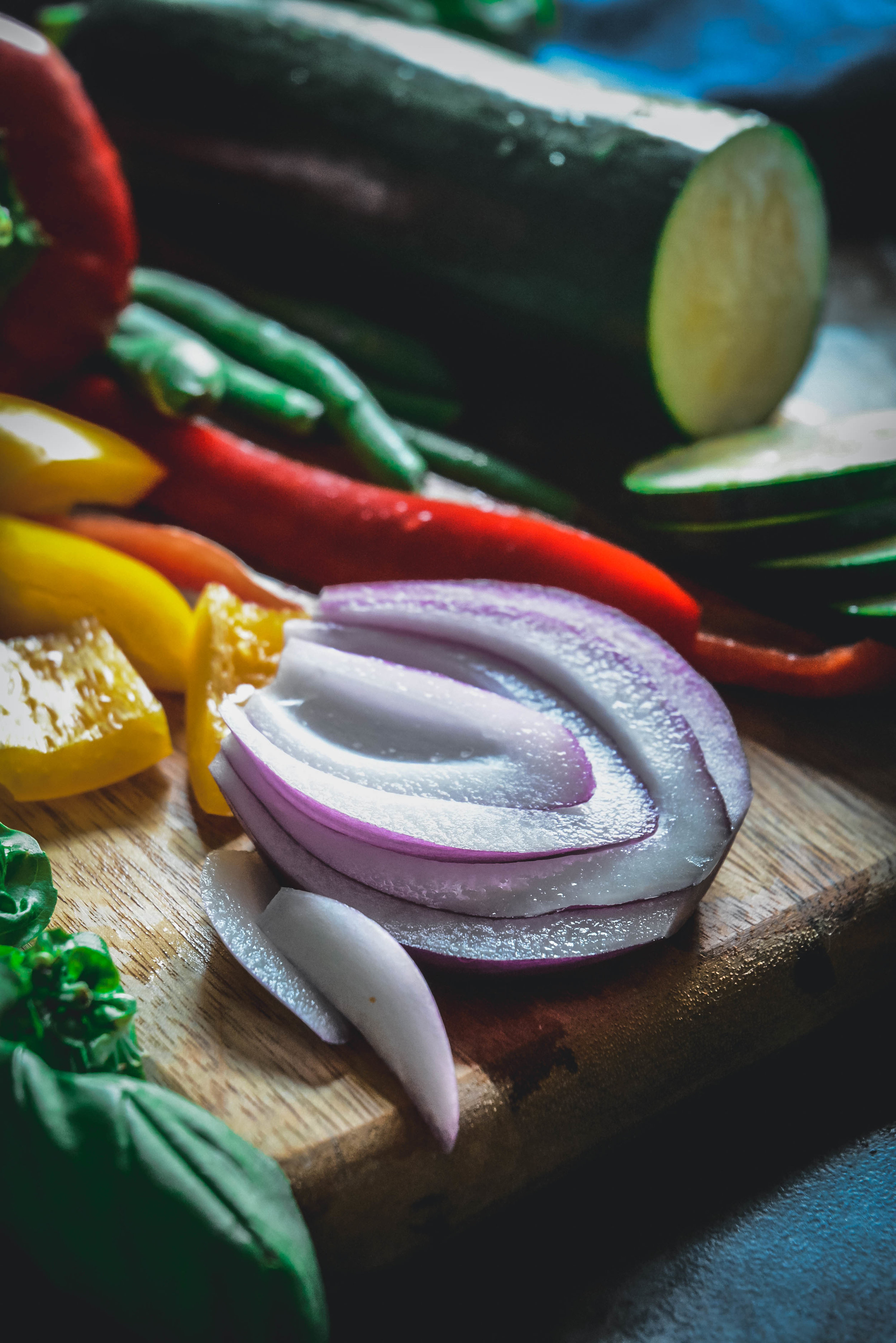 zucchini sliced, sliced red onion, sliced peppers on cutting board