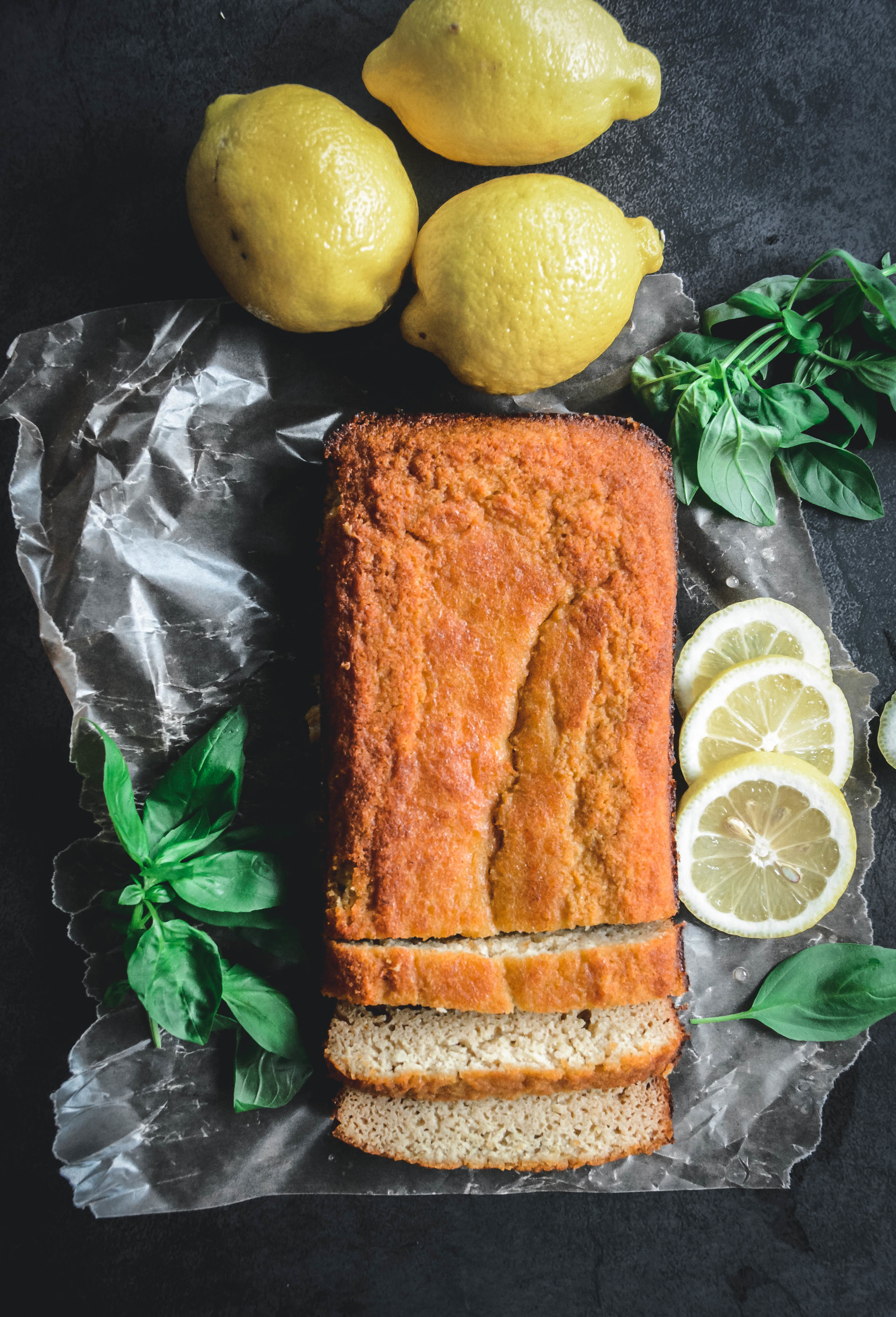 Loaf cake and lemons on table with greens