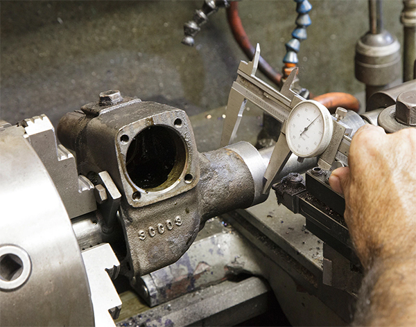A typical lathe operation that requires an operator to reach near a part while it may still be rotating from it's inertia.