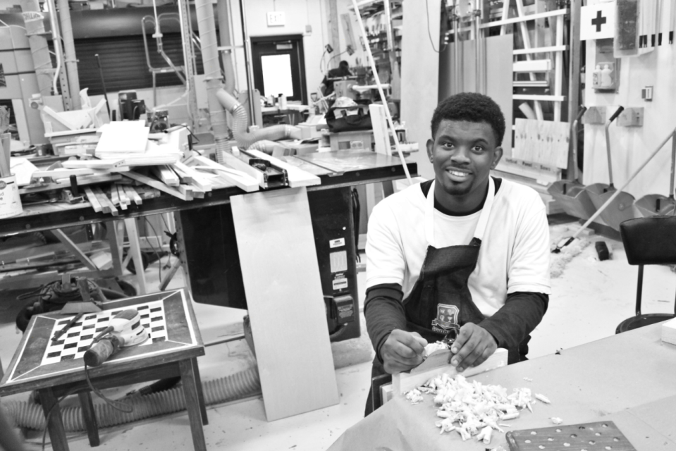 Student photograph of peer in wood-shop, Inspiring and Representing Occupational Pride Through Photography, 2020