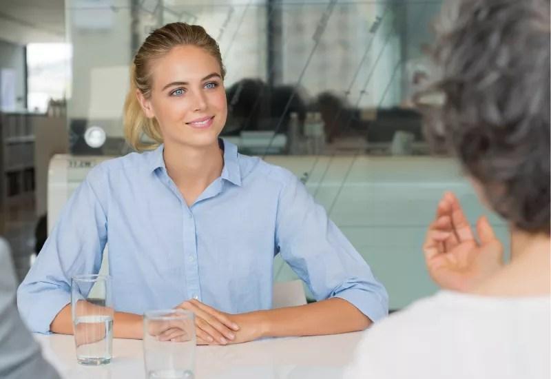 Kobieta siedzi przy stole podczas rozmowy rekrutacyjnej