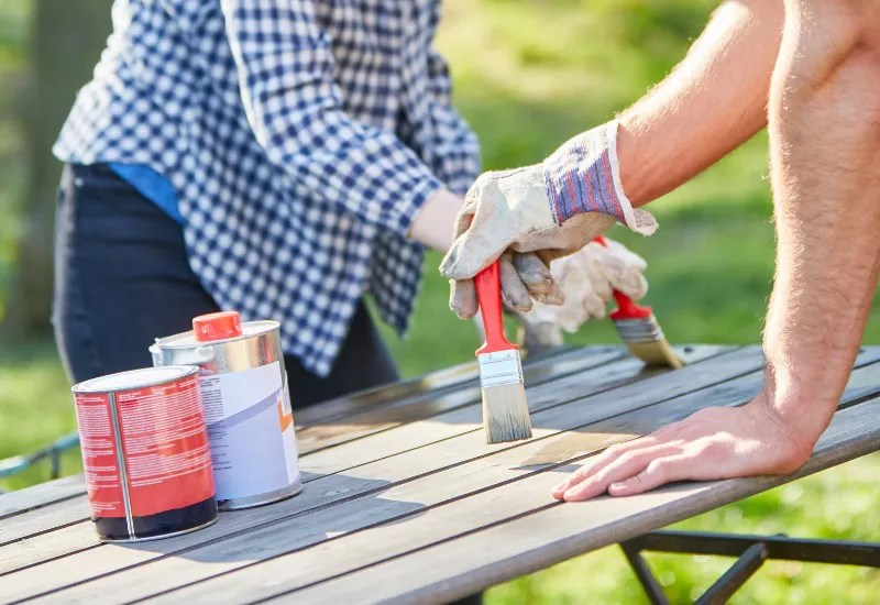 Couple painting furniture and renovating in the garden