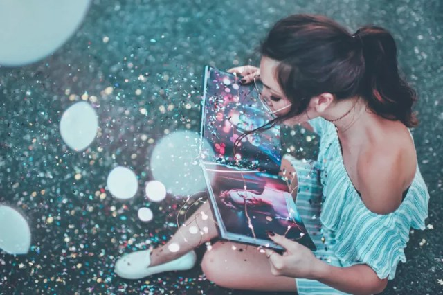 Girl reads a magical photo book with glitter