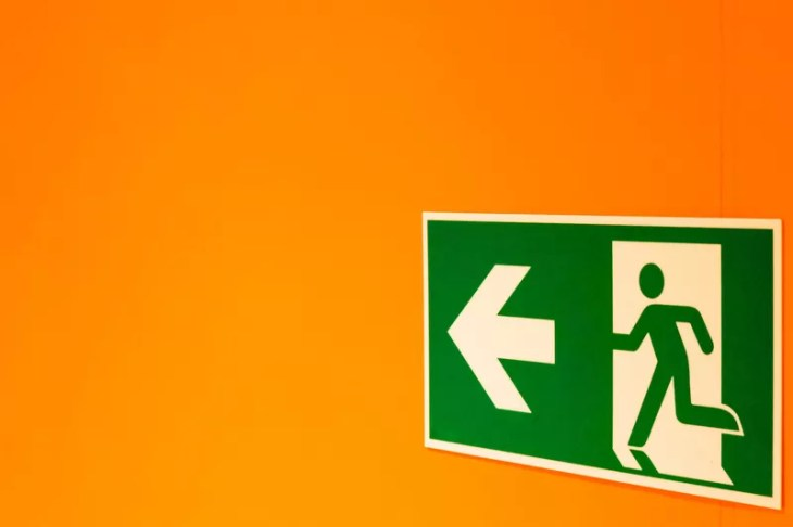 emergency exit sign on an orange wall
